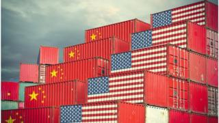 Shipping containers bearing US and Chinese flags