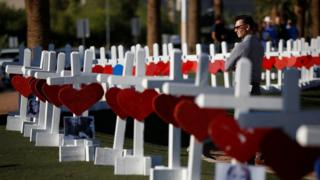 A man looks at the 58 white crosses set up for the victims of the Route 91 music festival mass shooting in Las Vegas