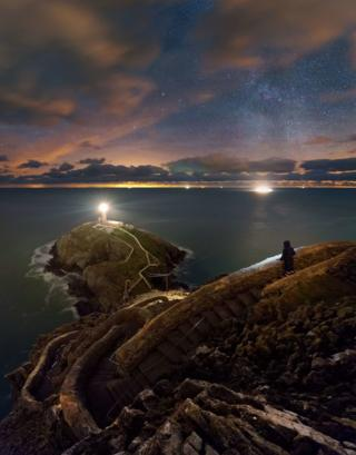 A fisherman looks out over a lighthouse on the coast of Anglesey in North Wales