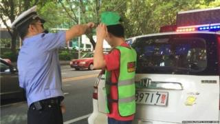 A police officer puts a green cap on a pedestrian who is also wearing a green vest