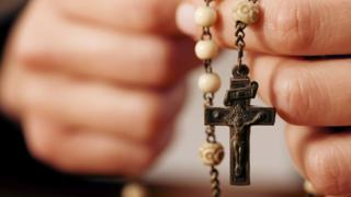 A woman holding rosary beads