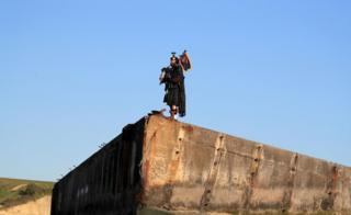 A lone piper plays on the Mulberry harbour at Arromanches in Normandy