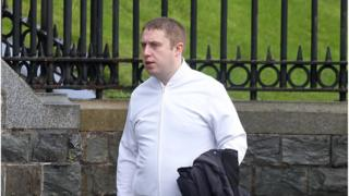 Domonic O'Connor walking, wearing a white shirt and holding a black jacket in left hand