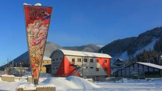 A triangular banner featuring the nude painting is seen displayed outside resort buildings in snowy Semmering