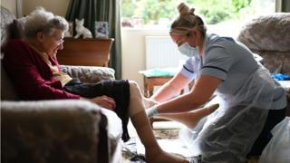 A care worker helps a care home resident put stockings on