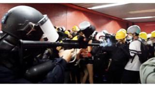 Полицейский стреляет в жителей Гонконга