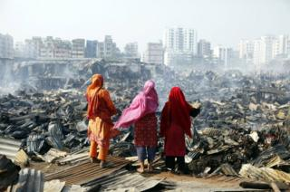in_pictures Three women look at the destroyed homes