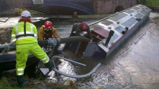 The Environment Agency and fire service personnel working to remove the boats