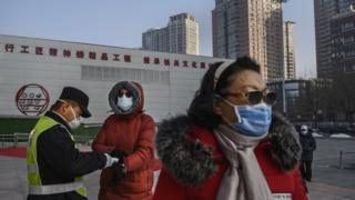 Donald Trump A Chinese woman (left) wears a protective mask as she has her temperature checked by an official entering a park on 9 February 2020 in Beijing, China
