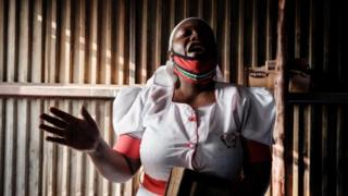 A worshipper of the African Divine Church attends a prayer at their church in the Kibera slum of Nairobi, on July 26, 2020, after Kenya's President allowed places of worship to reopen under strict guidelines to curb the spread of the novel coronavirus (COVID-19).