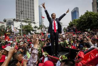 Indonesian President Joko Widodo waves to the crowd while on his journey to Presidential Palace by carriage during the ceremonial parade on 20 October 2014 in Jakarta, Indonesia.