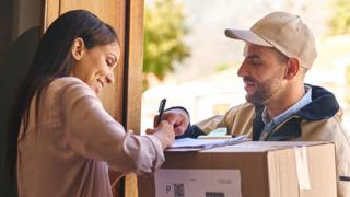 A woman signs for a parcel