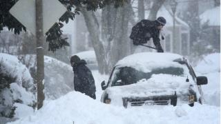People clear snow from their car in Arlington, Virginia in America.