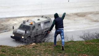 Palestinian throws stone at Israeli military vehicle in the West Bank, 8 January 2016