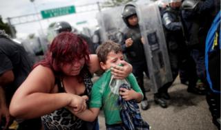 A woman covers her young son's mouth with his tshirt. Tear gas was fired by Mexican police as they tried to force back the crowd.
