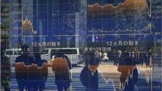 Pedestrians reflected in a window stand in front of a quotation board displaying the numbers on the Tokyo Stock Exchange in Tokyo.