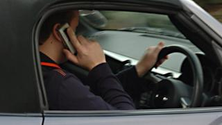 Posed file picture of a man using a mobile phone while driving.