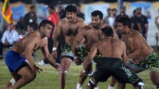 This file photograph taken on May 6, 2016, shows an Indian kabaddi player (L) as he attempts to tag a Pakistani opponent during their final match of the 3rd Asian Kabaddi Circle Style Championship 2016 in Wah some 45 kilometers from Islamabad.