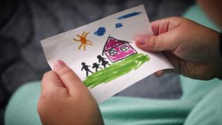 Child holding a children's drawing of a house and stick man, woman and child