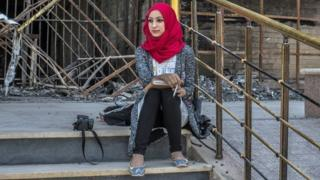 Student outside damaged building in Mosul University