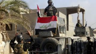 ラマディ市内でイラク国旗を掲げるイラク軍(28日)