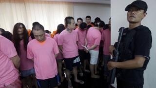This photo taken on July 31, 2017 shows an Indonesian policeman (in black) standing guard next to Chinese nationals who were arrested for alleged cyber fraud in Jakarta. Indonesia will deport 153 Chinese nationals arrested for alleged involvement in a multimillion-dollar cyber fraud ring targeting wealthy businessmen and politicians in China, police said on August 1