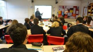 Teacher using white board during lesson