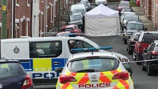 Police vehicles, a cordon and a tent erected at Melville Street