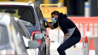 NHS workers check people at a coronavirus drive-through testing station set up at the Wembley IKEA store for NHS staff - 1 April 2020