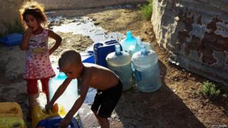 Syrian children fill jerry cans with water at a pump inside a camp for refugees in Baalbek, Lebanon