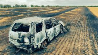 Burnt car and field
