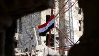 علم سوري على بناية دمرت خلال الحرب المستمرة منذ سنوات