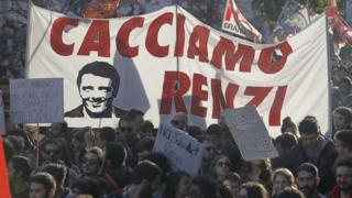 """People march behind a banner portraying Italian premier Matteo Renzi and reading """"Let's oust Renzi"""" during a demonstration ahead of a referendum over a constitutional reform."""