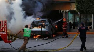 Firefighters work on a burning car outside a store after an operation by security forces against organized crime in Celaya, in Guanajuato state, Mexico June 20, 2020