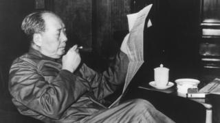 Mao Zedong, reading a newspaper and smoking a cigar, in an image dated 1963