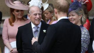 The Duke of Edinburgh laughs with his grandson, Prince Harry
