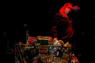 A woman wearing a face mask stands next to a shopping trolley full of food