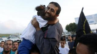 Khader Adnan hugs his daughter as he arrives home in the village of Araba, near the West Bank City of Jenin, 12 July 2015
