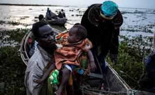 Dis family dey among thousands wey don run comot from eastern DR Congo, because of violence, dem boat take cross Albert to reach Uganda.