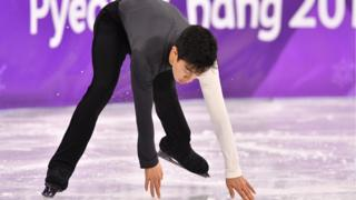 USA's Nathan Chen touches the ice as he skates during the men's short program