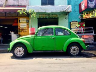 Green Volkswagen Beetle parked in front of some buildings