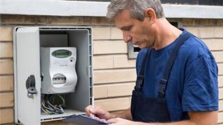 Man checking electric meter