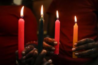 Two pink candles, one green and one yellow are seen close up, held in the hands of two different people who are both wearing red tops in Nairobi, Kenya - Sunday 17 February 2019