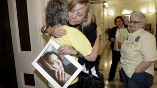 Debbie Ziegler - holding a photo of her daughter, Brittany Maynard - hugs a supporter after the measure was passed