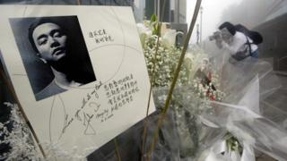 People leave flowers in memory of entertainer Leslie Cheung prior to queuing outside Madame Tussaud waxworks in Hong Kong for a viewing of the waxwork model of Cheung, 31 March 2004