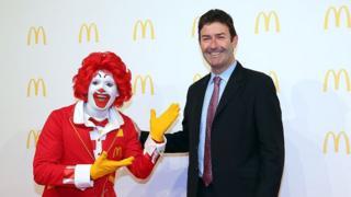O palhaço que representa o McDonald's sorri e posa ao lado do CEO da empresa, Steve Easterbrook
