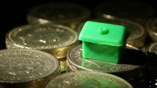 A Monopoly house sits among pound coins