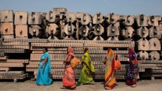Devotees walk past pillars in the city of Ayodhya, India