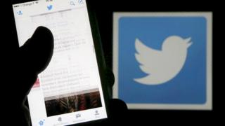 mobile phone in hand and Twitter logo