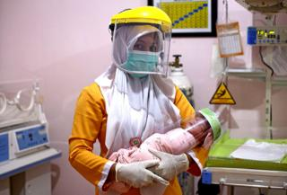 An Indonesian nurse wearing protective gear holds a newborn baby, also wearing a face shield